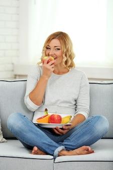 Hermosa mujer con frutas frescas en la superficie interior de una casa