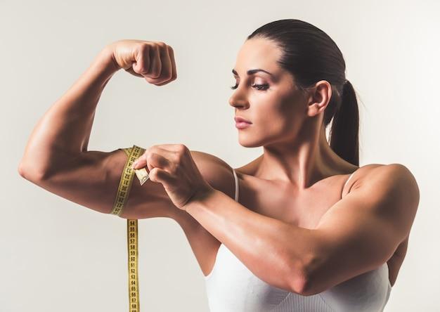 Hermosa mujer fuerte está midiendo sus bíceps.