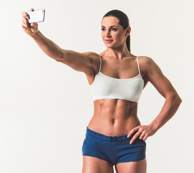Hermosa mujer fuerte en ropa deportiva está haciendo selfie.