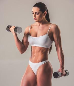 Hermosa mujer fuerte en ropa interior blanca con pesas.