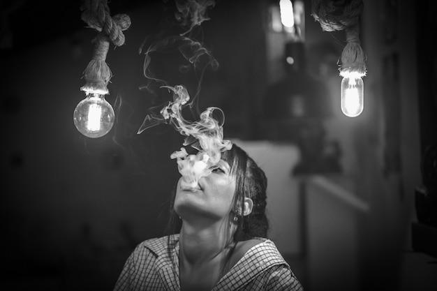 Hermosa mujer fumando cigarrillo electrónico