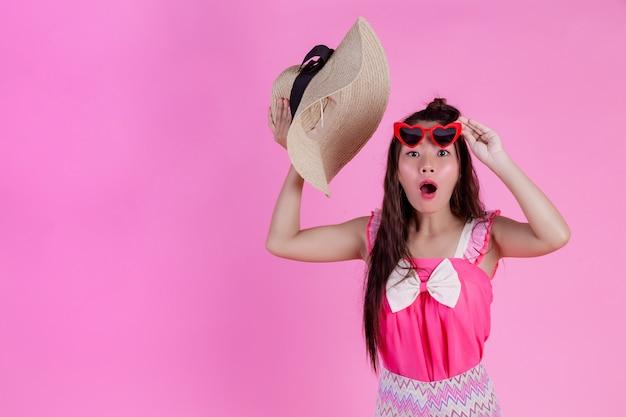 Una hermosa mujer con gafas rojas con un gran sombrero en un rosa.