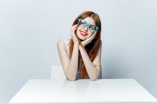 Hermosa mujer con gafas se sienta en una mesa, espacio de luz, posando emociones