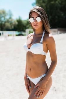 Hermosa mujer en gafas de sol en bikini
