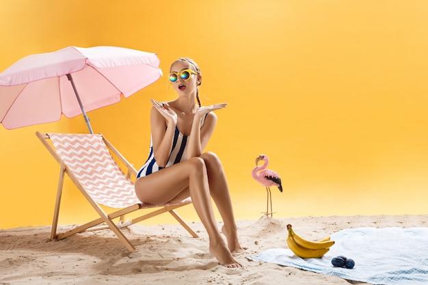 Hermosa mujer con gafas de sol coloridas parece sorprendida sobre fondo brillante