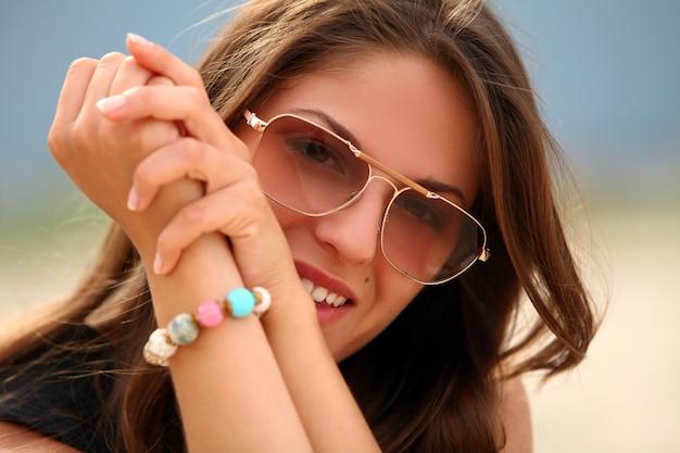 Hermosa mujer con gafas de sol en la playa
