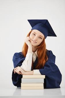 Hermosa mujer graduada con libros sonriendo.