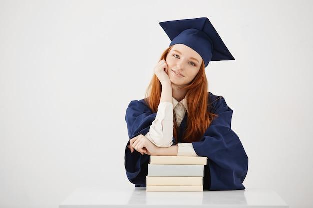Hermosa mujer graduada sentada con libros sonriendo.
