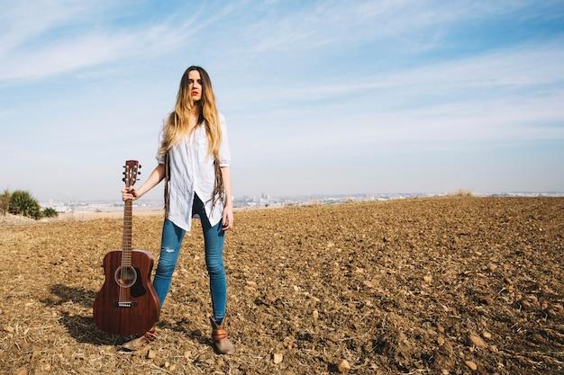 Hermosa mujer con guitarra en la naturaleza