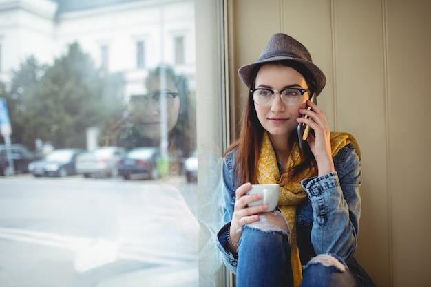 Hermosa mujer hablando por celular en el café