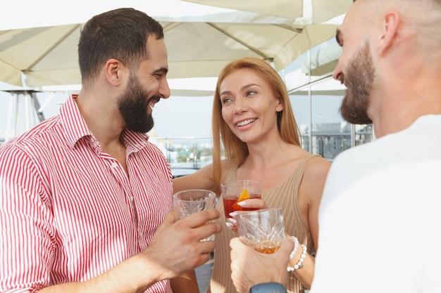 Hermosa mujer hablando con sus amigos varones con bebidas en una fiesta en la azotea
