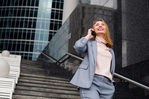 Hermosa mujer hablando por teléfono caminando en la calle. retrato de elegante mujer de negocios sonriente en ropa de moda llamando por teléfono móvil cerca de la oficina