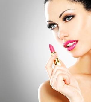 Hermosa mujer hace maquillaje aplicando lápiz labial rosa en los labios