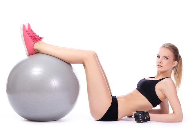Hermosa mujer haciendo ejercicios abdominales con pelota de fitness