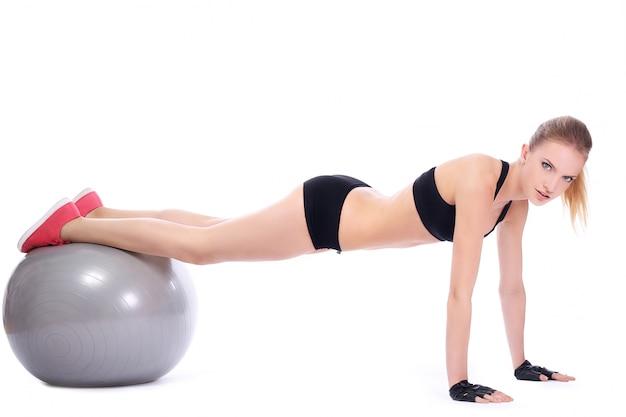 Hermosa mujer haciendo flexiones en la bola de la aptitud