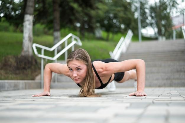 Hermosa mujer haciendo flexiones