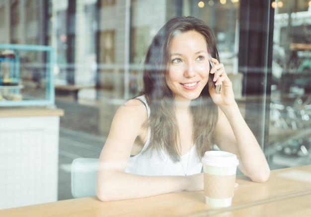 Hermosa mujer haciendo llamadas telefónicas dentro de una tienda