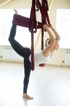 Hermosa mujer haciendo natarajasana yoga plantean en hamaca