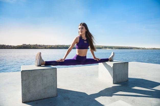 Hermosa mujer haciendo split en un cálido día de verano. concepto de estilo de vida activo deportivo