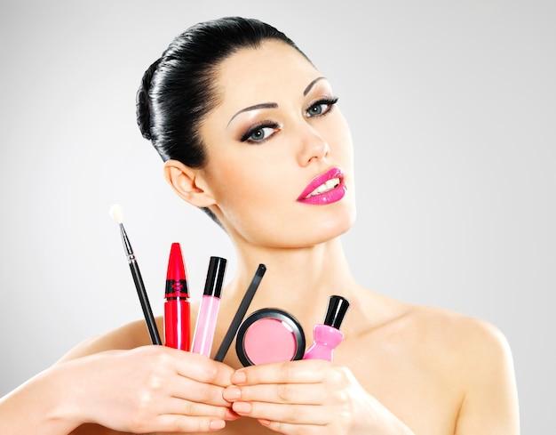 Hermosa mujer con herramientas cosméticas de maquillaje cerca de su rostro.