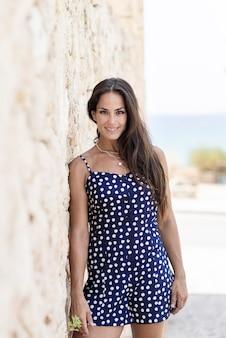 Hermosa mujer hispana en vestido azul, apoyado en la pared mientras mira a la cámara