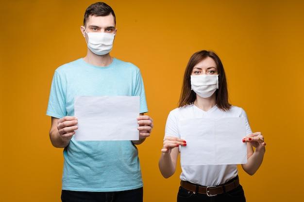 Hermosa mujer y hombre guapo se encuentra cerca el uno del otro en camisetas blancas y azules y máscaras médicas blancas y sostiene hojas de papel