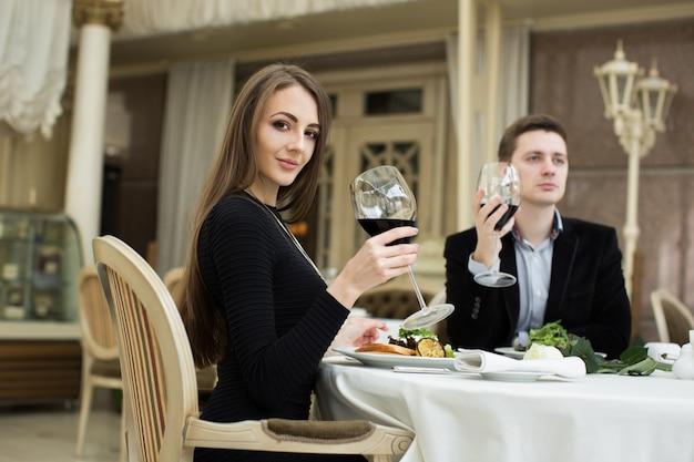 Hermosa mujer y hombre en restaurante, sosteniendo una copa de vino