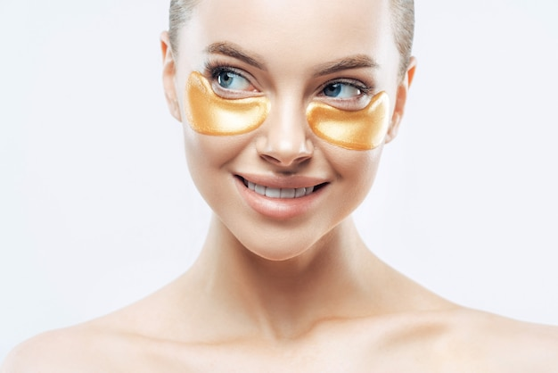 Hermosa mujer con hombros desnudos, realiza una rutina diaria de cuidado facial, aplica parches dorados debajo de los ojos