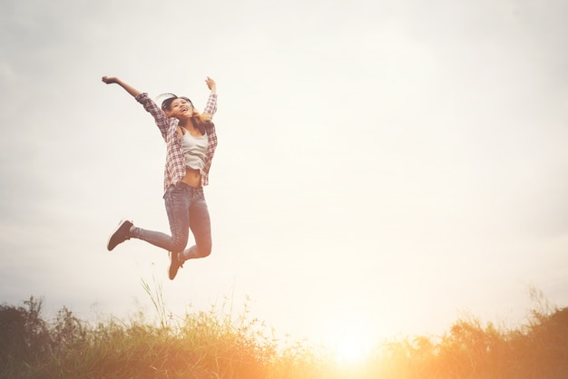 Hermosa mujer inconformista saltar alto, disfrutando de la libertad con la
