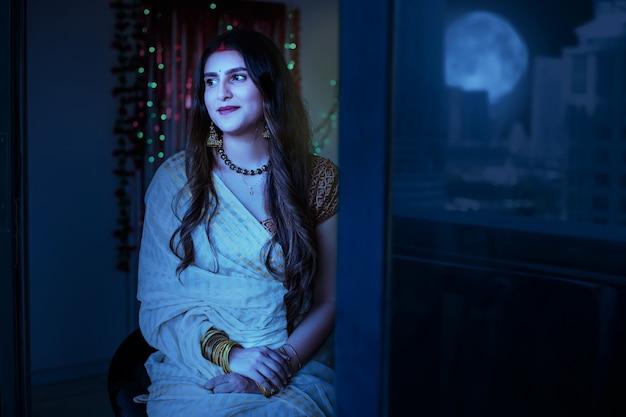 Hermosa mujer india mirando a la luna en la noche de karva chauth