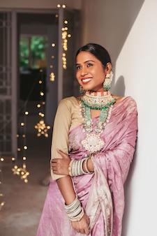 Hermosa mujer india en sari banarasi malva y joyería nupcial pesada