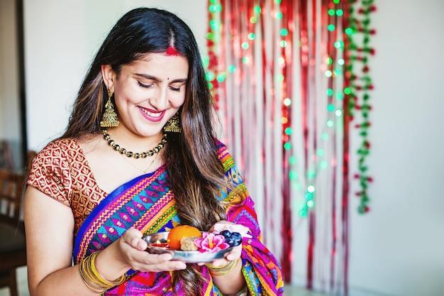 Hermosa mujer india sosteniendo thali en diwali