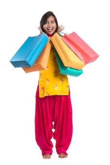 Hermosa mujer india en un traje tradicional con bolsas de compras