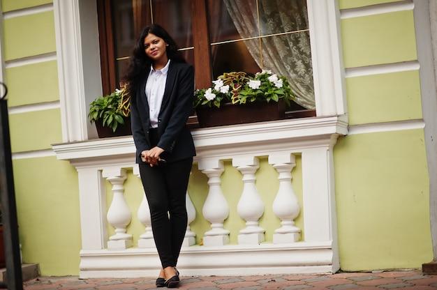 Hermosa mujer india usa posando formal en la calle con el teléfono móvil en las manos.
