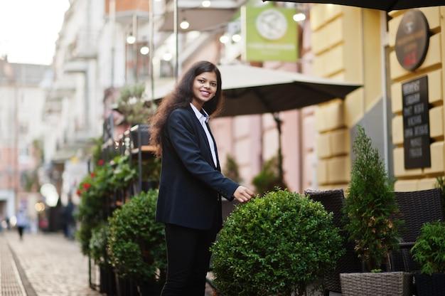 Hermosa mujer india usa posando formal en la calle.