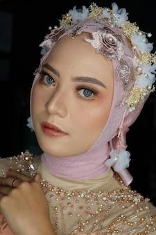 Hermosa mujer indonesia musulmana con hijab y flores