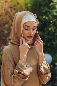 Hermosa mujer islámica en un vestido musulmán de pie en un parque de verano fondo de la calle bosque árboles otoñales