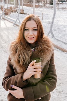 Hermosa mujer de jengibre bebiendo té caliente de termo taza