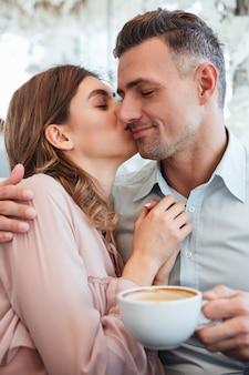 Hermosa mujer joven abrazando y besando a su novio masculino en el acogedor café de la ciudad, mientras que el hombre contento bebiendo té o café