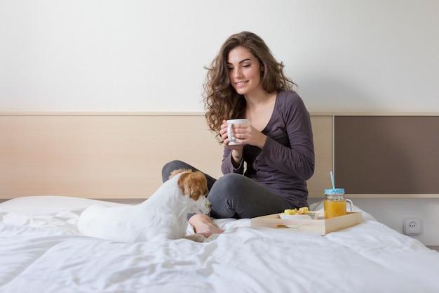 Hermosa mujer joven acostada en la cama con su pequeño perro lindo además.