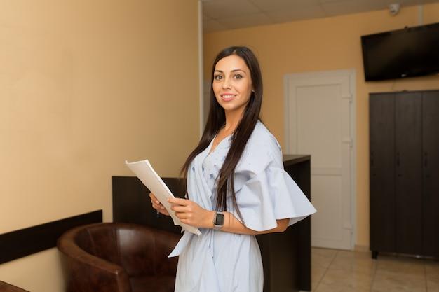 Hermosa mujer joven administrador en recepción mantenga carpeta con papeles.