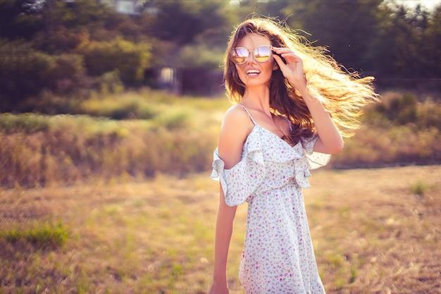 Hermosa mujer joven al aire libre en la colina en un día de verano