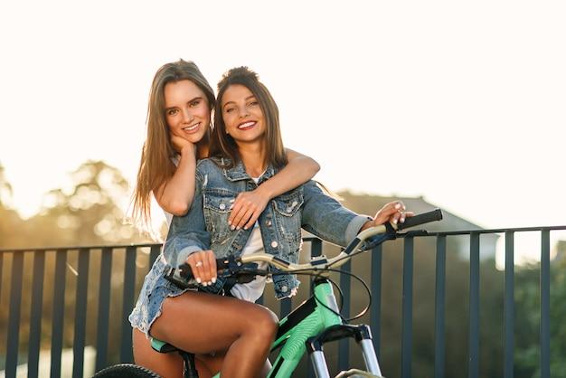 Hermosa mujer joven alegre abrazando a su encantadora amiga sentada en la bicicleta y mirando a la cámara con una bonita sonrisa en el fondo del atardecer
