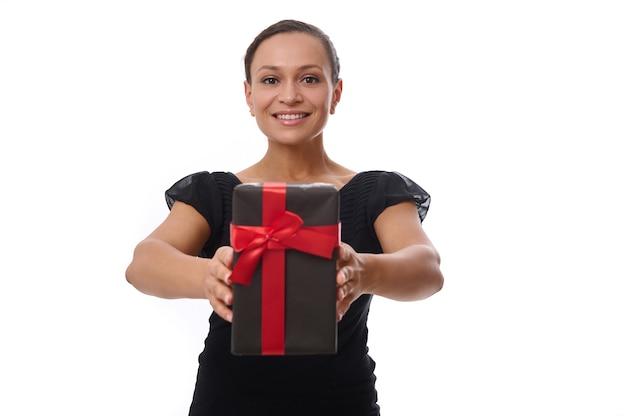 Hermosa mujer joven alegre hermosa de etnia afroamericana vestida de negro y sonríe con una gran sonrisa, sostiene un regalo negro con cinta roja y se lo muestra a la cámara. concepto de viernes negro