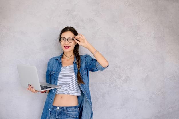 Hermosa mujer joven en anteojos de pie con una computadora portátil en sus manos