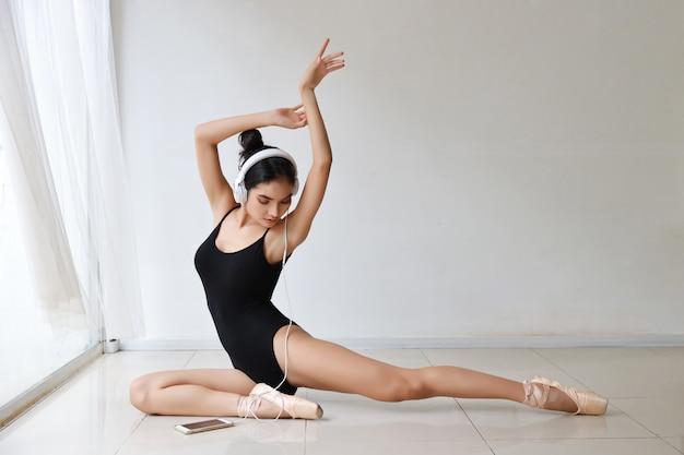 Hermosa mujer joven asiática saludable con auriculares, escuchando música desde el teléfono móvil mientras entrena ballet