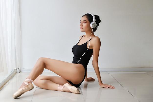 Hermosa mujer joven asiática sana y deportiva en ropa deportiva negra con auriculares, escuchando música desde el teléfono móvil mientras entrena ballet