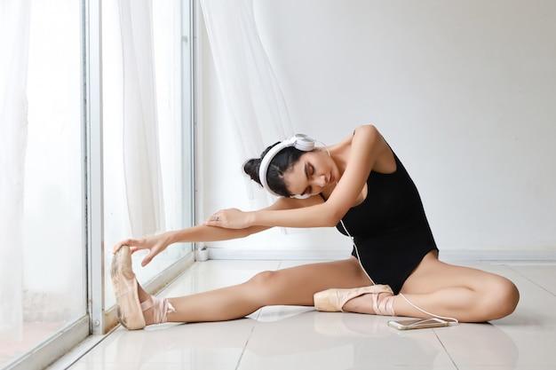 Hermosa mujer joven asiática sana y deportiva en ropa deportiva negra con auriculares, practicando ballet desde el teléfono móvil