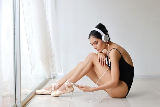 Hermosa mujer joven asiática sana y deportiva en ropa deportiva negra con auriculares, usando el teléfono celular mientras practica ballet