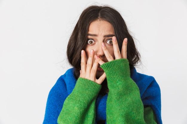 Hermosa mujer joven asustada confundida vestida con un suéter verde posando aislada en la pared blanca cara coning.